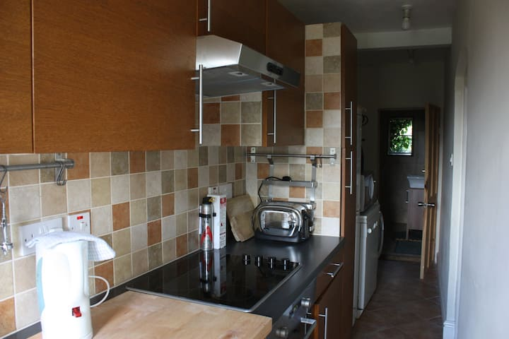 Compact but fully equipped kitchen, with the bathroom visible at the end.
