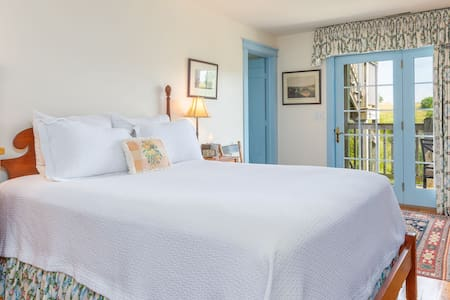 Queen room with tempur-pedic mattress and premium linens sourced from the UK, private bathroom, and private porch with views of the rolling countryside.