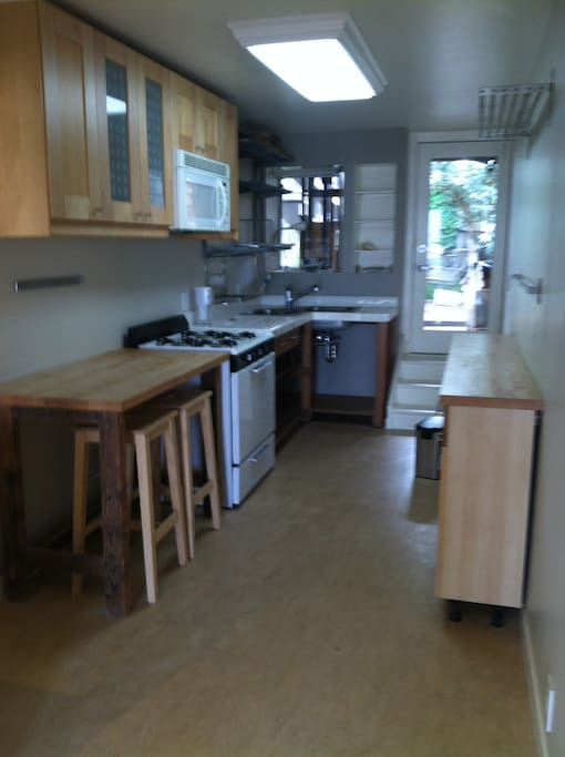 The eat-in kitchen with refrigerator, stove, sink, microwave, seating counter, work counters, shelving and cabinetry.