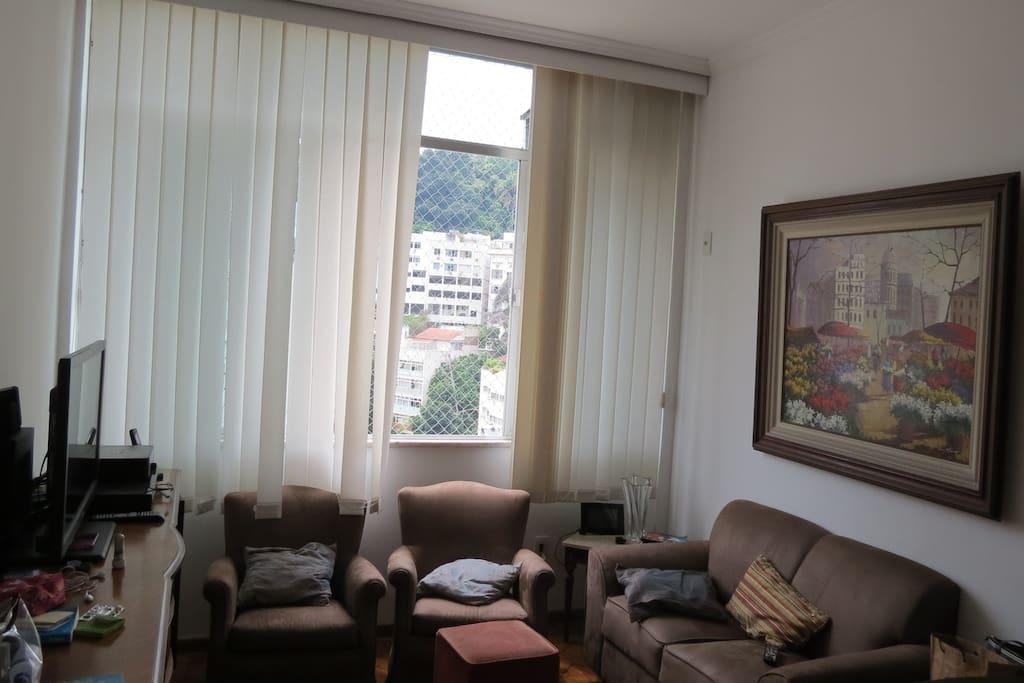 Sala com TV, home theatre, adega de vinho, mesa de 6 lugares, 1 sofá de 2 lugares e 2 poltronas