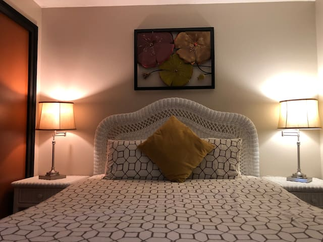 BEDROOM 2 with comfortable Queen  bed with night stands, night lights, and dresser. Easy access to outlets