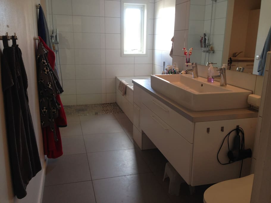 Main bathroom with underfloor heating, shower and bathtub and entrance to washingroom