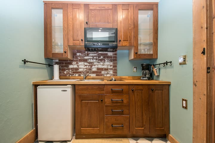 Kitchenette with two burner cooktop, microwave and mini refrigerator