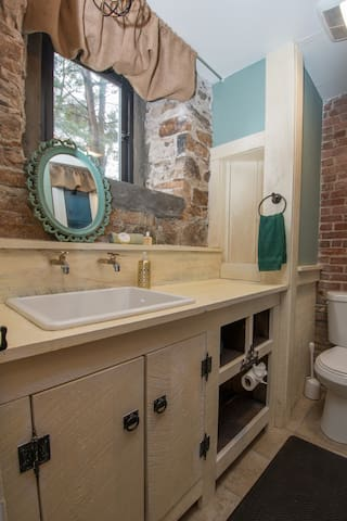 The old servant's wash sink functions as a beautiful bathroom counter