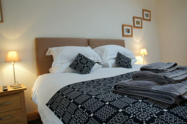 Comfortable bedroom with zip and link bed and ensuite in farm self catering cottage near Criccieth