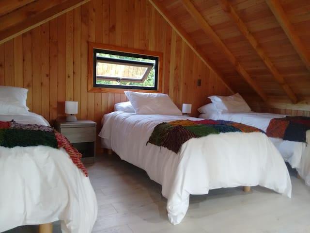 Dormitorio en altillo con 3 camas de una plaza cada una