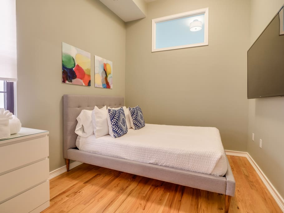 The queen-size bed in the second bedroom has an elegant tufted headboard and promises a luxurious sleeping experience.