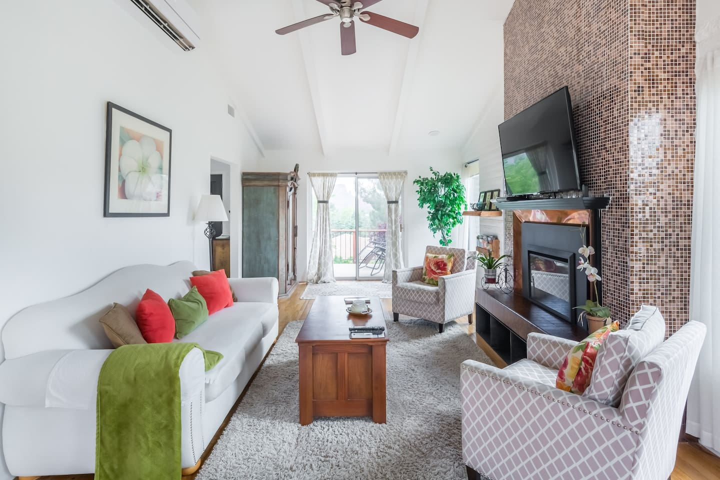 Spacious, comfortable living room with TV, electric fireplace and amazing panoramic views of the red rocks. Wine cooler in main armoire.
