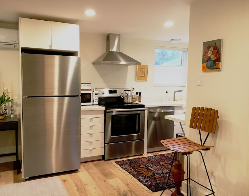 Full kitchen with stainless steel refrigerator, range with ceramic cooktop, externally-vented hood and dishwasher.
