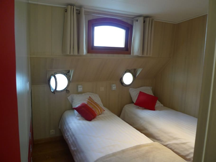 Twin bedded red room with porthole view on the water.
