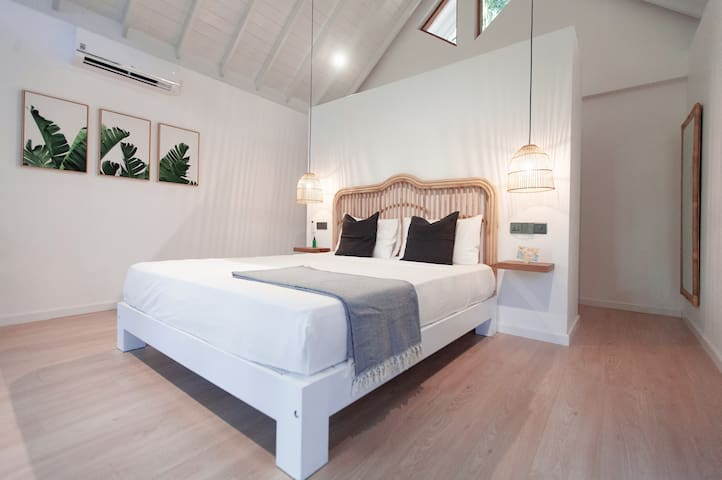 Bright air-conditioned room with high pitched ceiling and linen-adorned king-sized bed.