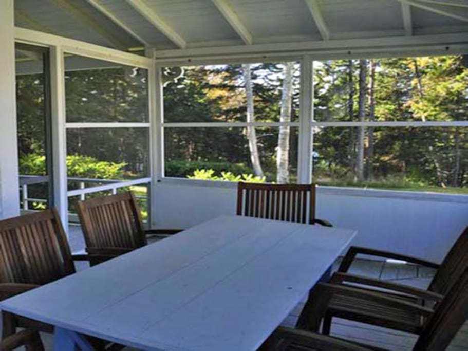 A nice screened in porch with a large dinner table.