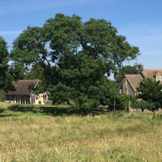 View from the surrounding fields, showing proximity of The Doghouse to the main house.