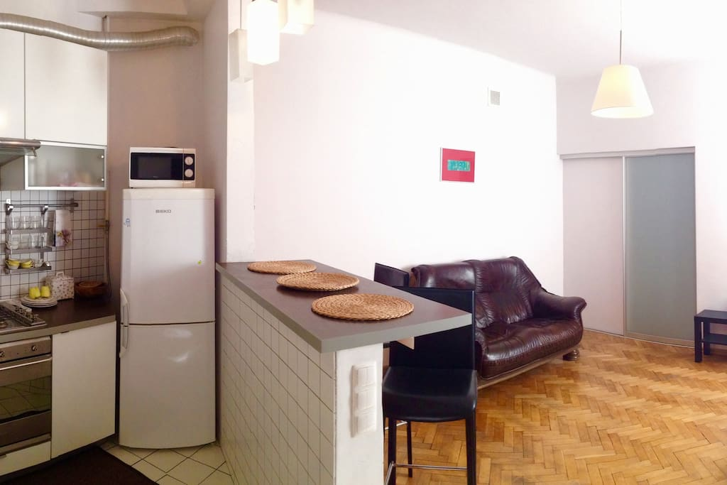 Kitchen and living room with refrigerator, microwave, gas stove, build in oven, dishes, bar stools, leather sofa