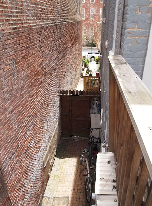 Side of house, walk through this space to walk up to apartment.  Private and very quiet area.