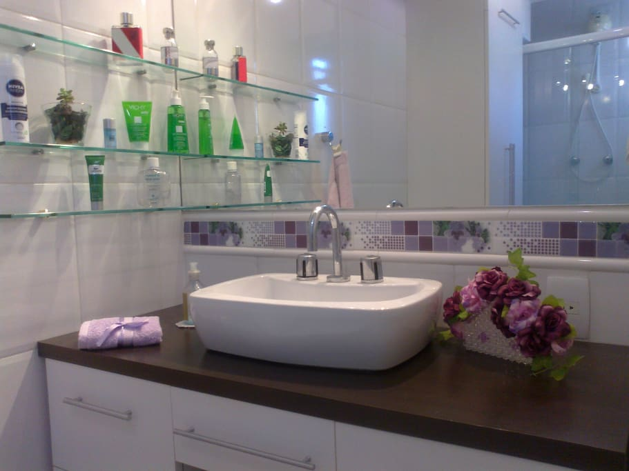 Lavatório com amplo espelho e secador de cabelos.