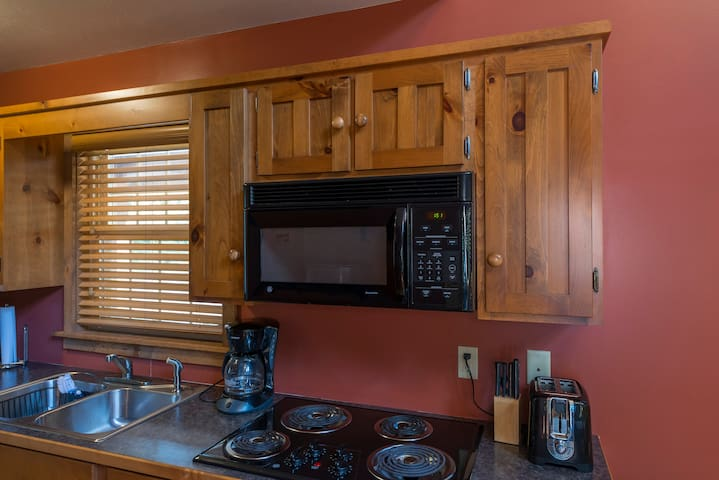 Fully equipped kitchen with coffeemaker, toaster, oven, microwave, and fridge