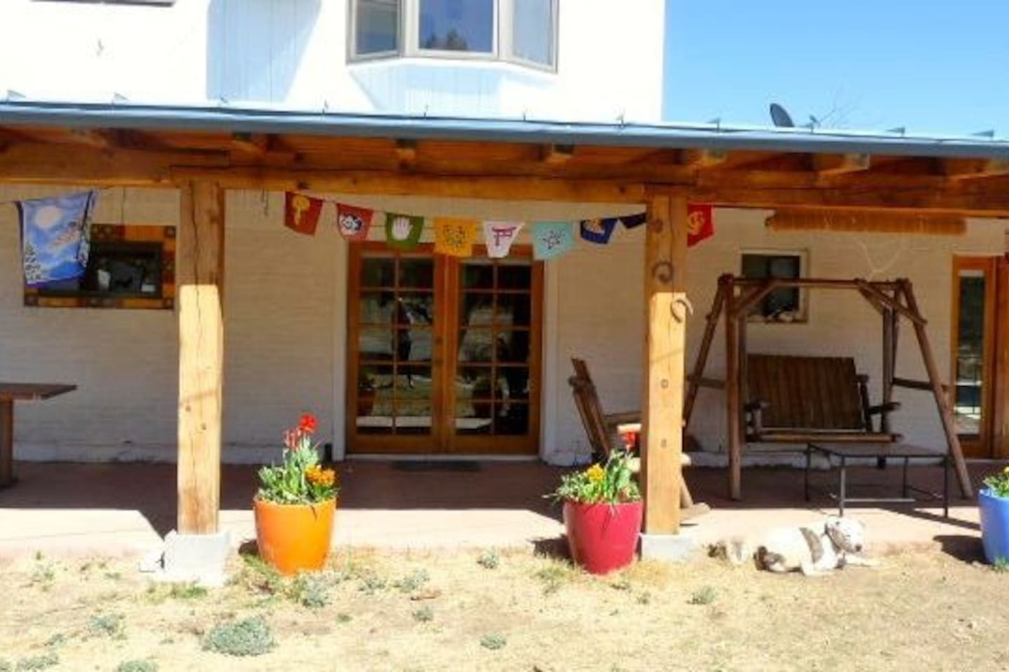 flag-lined front porch with swinging bench and rocking chair