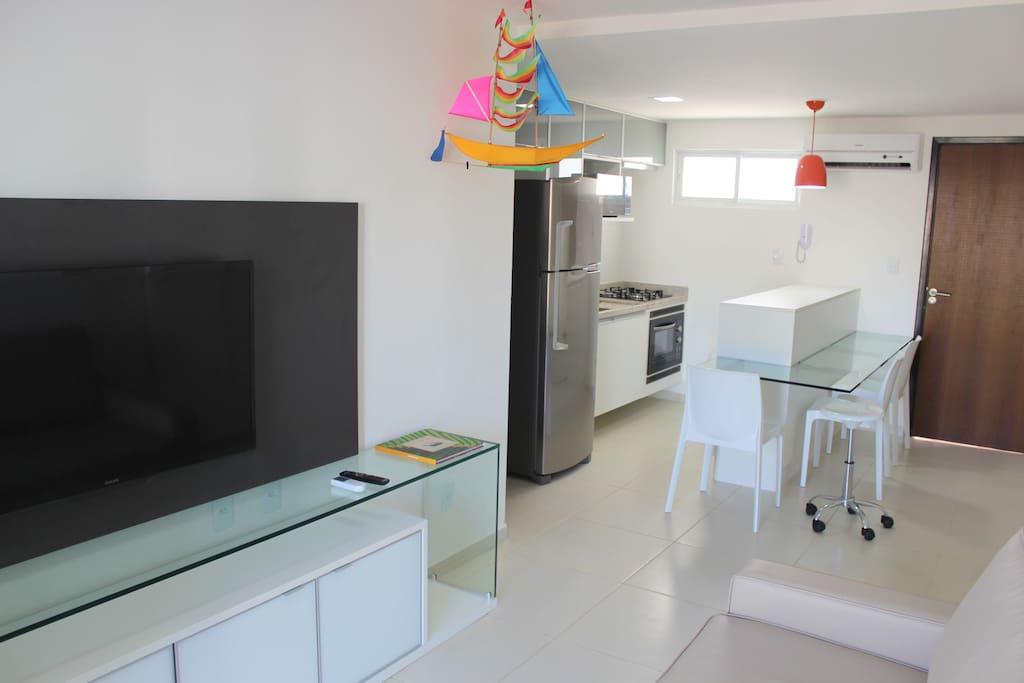 Vista da cozinha com cooktop, forno de embutir elétrico, exaustor, geladeira duplex, microondas,  ilha com 4 lugares,  armários e utensílios.