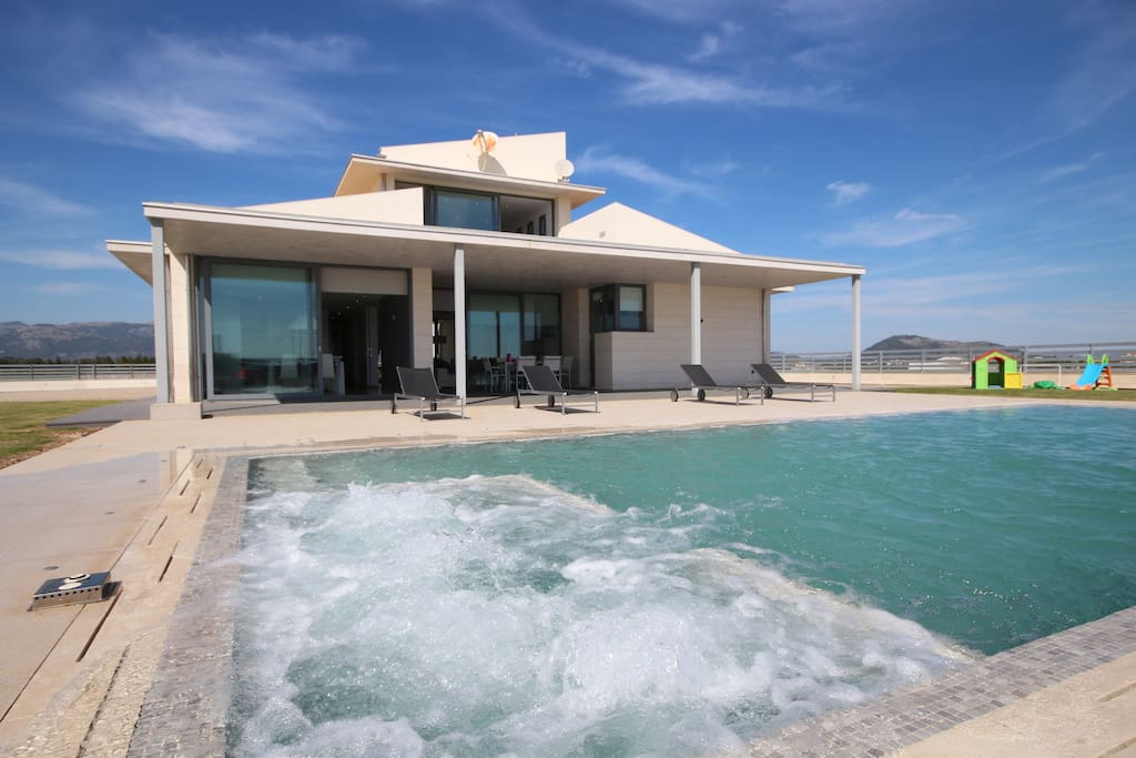 Large pool laid out, with bubbling jacuzzi, shower and modern sun beds.