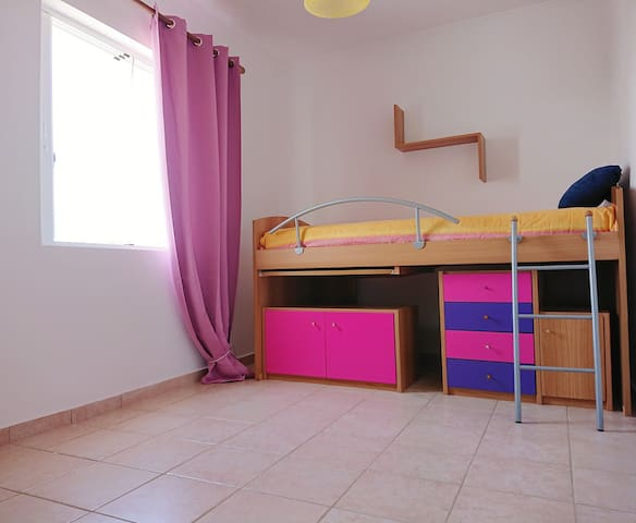 Kids room with high sleeper bed and built-in desk. Can also host an adult. Window with sea view, system with cabinets and drawers under sleeping area. Closet wall with cabinets and drawers on the opposite wall.