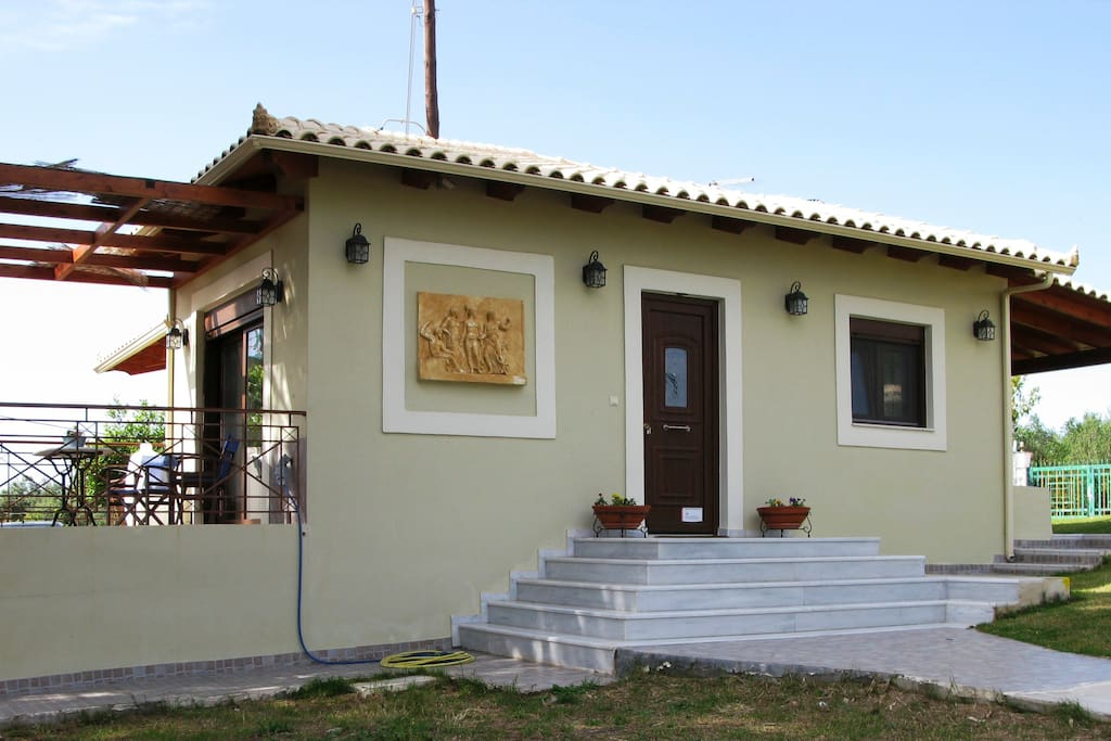 Exterior view, house 1 - garden, main entrance and side porch with beautiful sea view