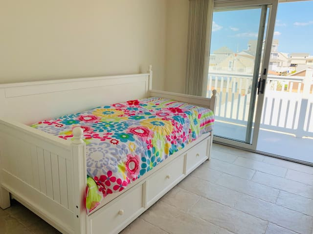 This bedroom offers two twin beds via a trundle bed, large closet with closet organizer offering lots of shelving and room for handing clothes. Sliding glass doors offer lots of natural light and access to the rear deck.