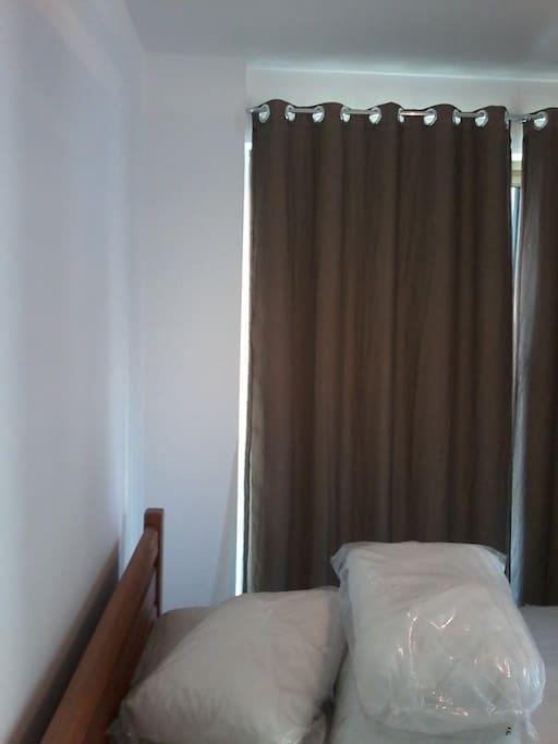 quarto com cama de casal, cortina e ar condicionado