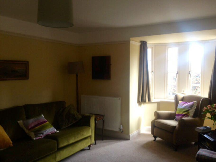 Cosy sitting room, with open fire and comfortable seating for eight people.