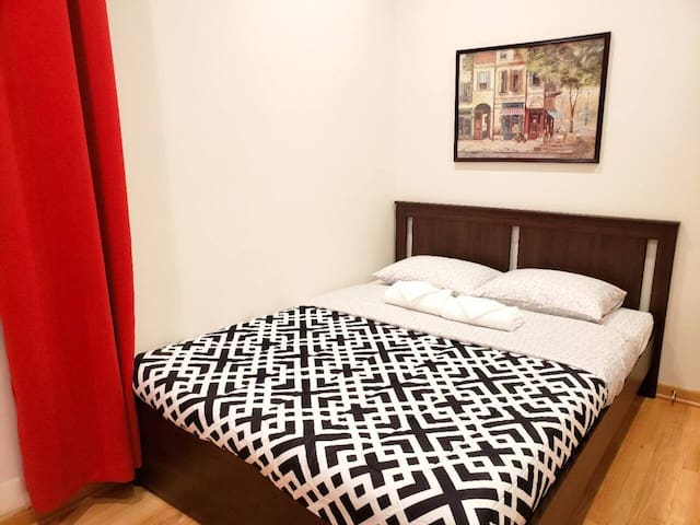 Bedroom 1: Queen-sized bed with GREEN TEA & ALOE memory foam mattress, fresh linens and towels, and full-sized mirror.