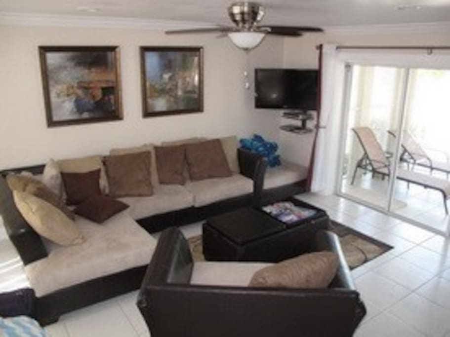 The living room is beautiful appointed with all new furniture and large white tile floors throughout.