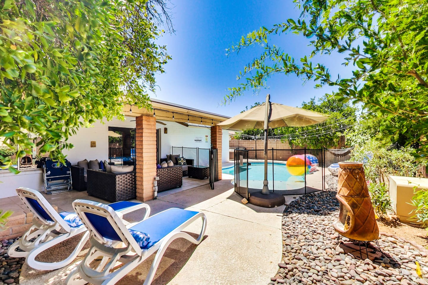Large pool with cantilever umbrella and comfortable chaises by the pomegranate tree