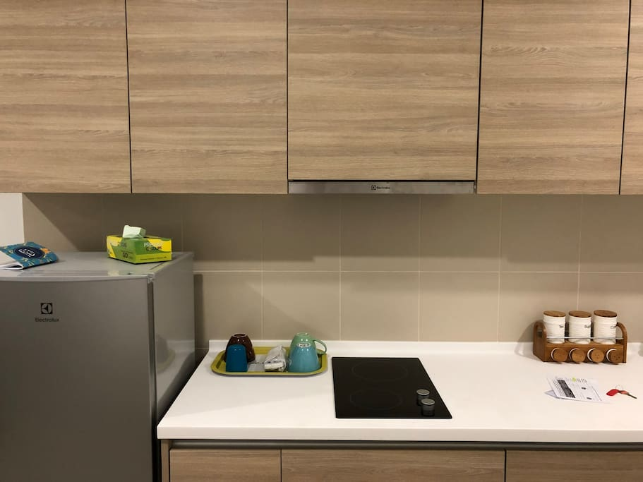 A very functional kitchen, with one-door refrigerator, hood & hob, kettle, rice cooker, toaster and other kitchen utensils.