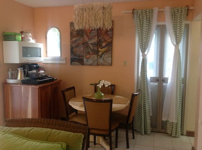 Living/Dining room with 4 seater dining table, microwave & coffee maker