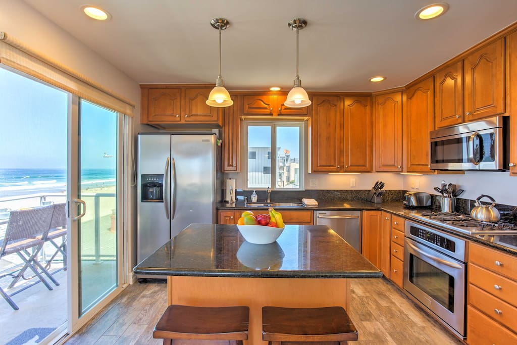 Cooking will be a breeze in this fully equipped kitchen with stainless steel appliances, breakfast bar, and ocean views.