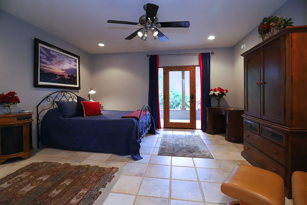 The Blue Room - large bedroom with Queen bed desk, armoire with TV and kitchenette.