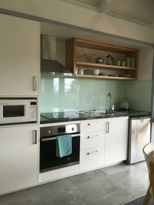 Fully equipped kitchen with fridge, microwave and oven