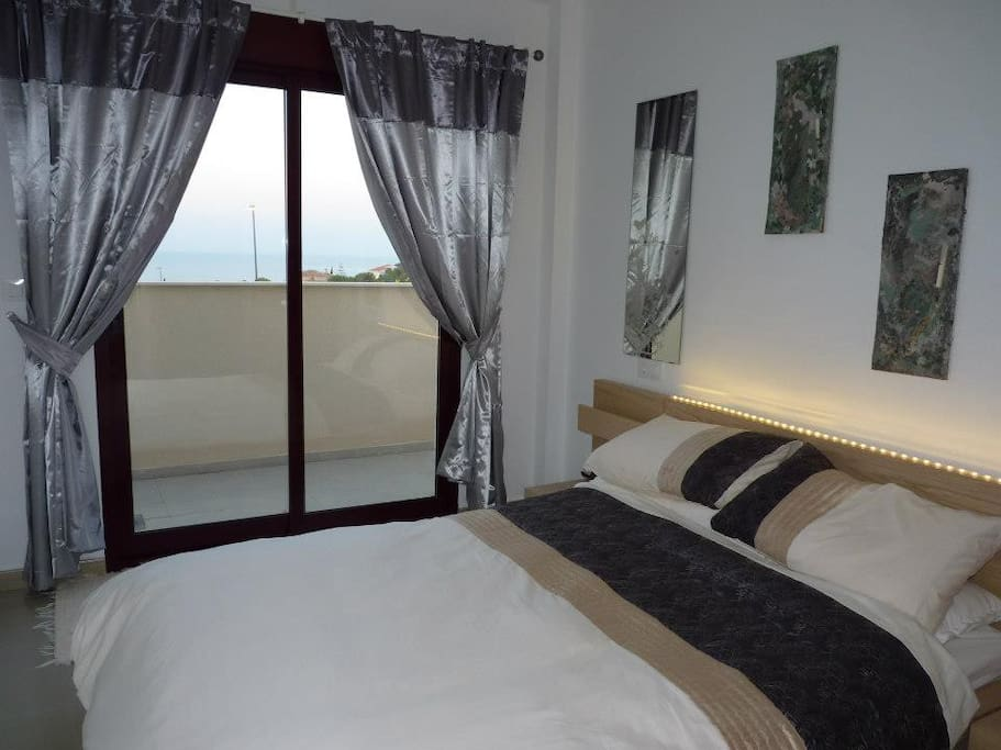 king size bed with sliding door to massive terrace, garden and beautiful seaview and sunsets