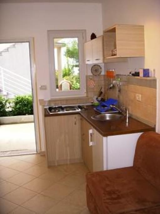 The kitchen is equipped with a fridge, toaster, and cooking utensils, Tea kettle, table and chairs.