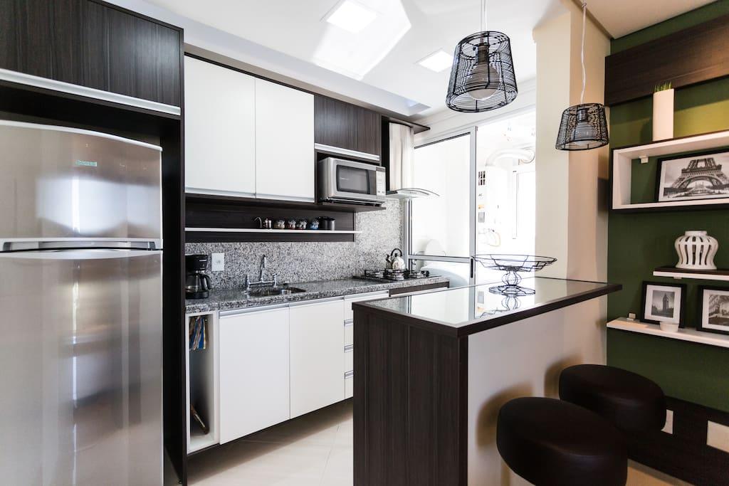 Cozinha com bancada e 02 bancos altos.