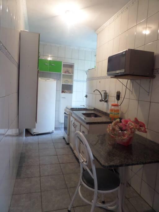 Cozinha com armário, refrigerador, mesa de 4 lugares, microondas e fogão.
