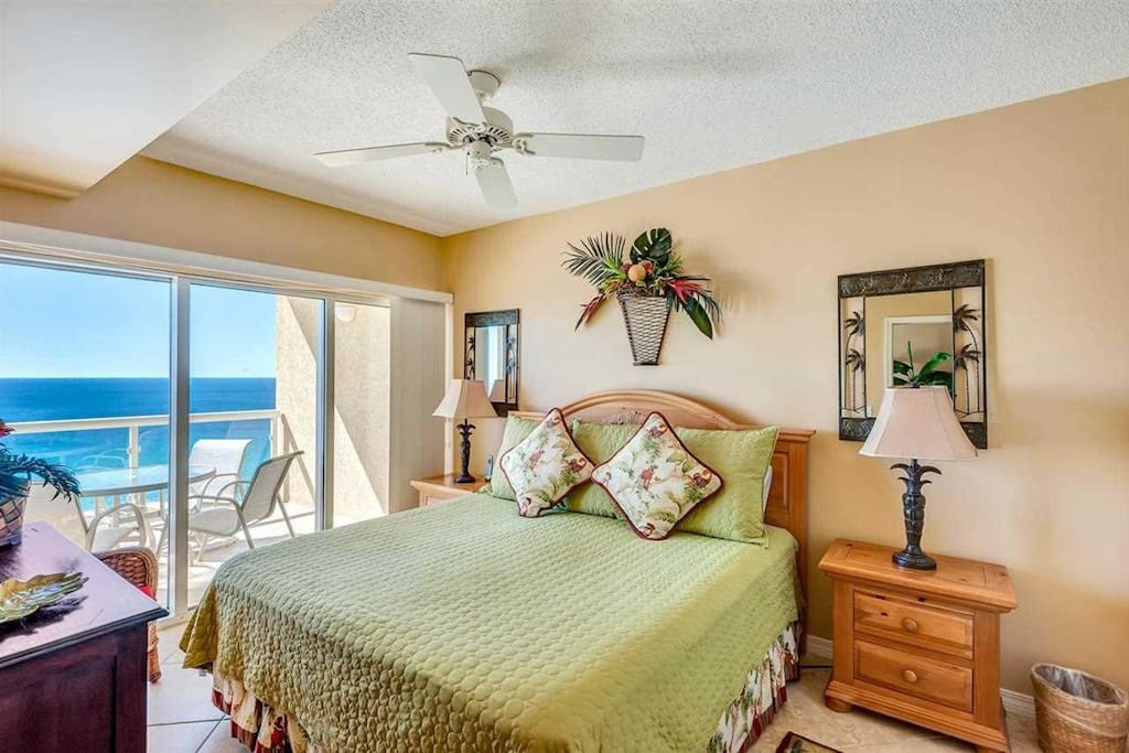 Master bedroom with access to private balcony overlooking sugar white sand beach and emerald waters