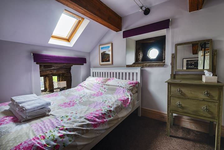A small but perfectly formed bedroom, which has a double bed, dressing table and a storage rail to hang clothes.