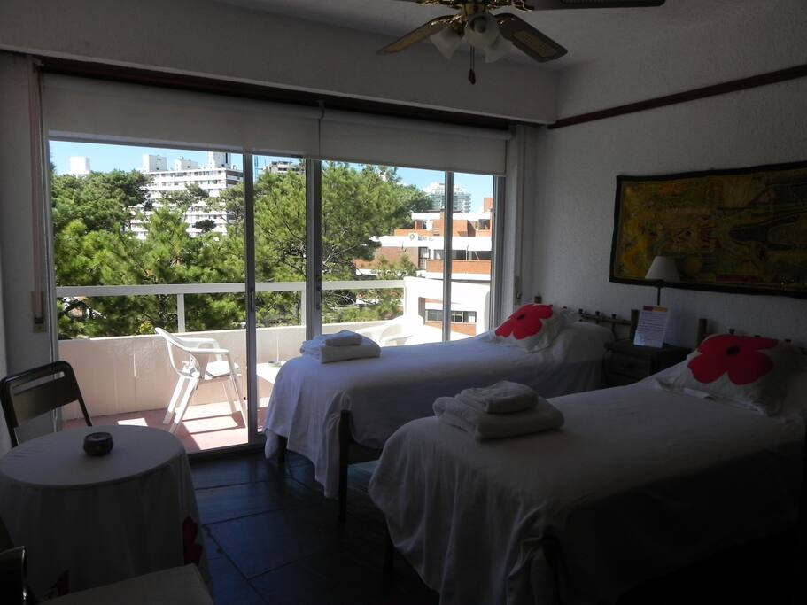 Orange room with twin beds and private balcony.