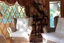 A comfortable loveseat and chair are provided in the Yurt.