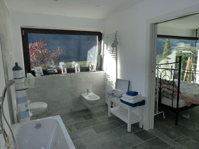 Das angrenzende Bad ist mit Badewanne barrierefreier Dusche WC Waschbecken und Bidet ausgestattet