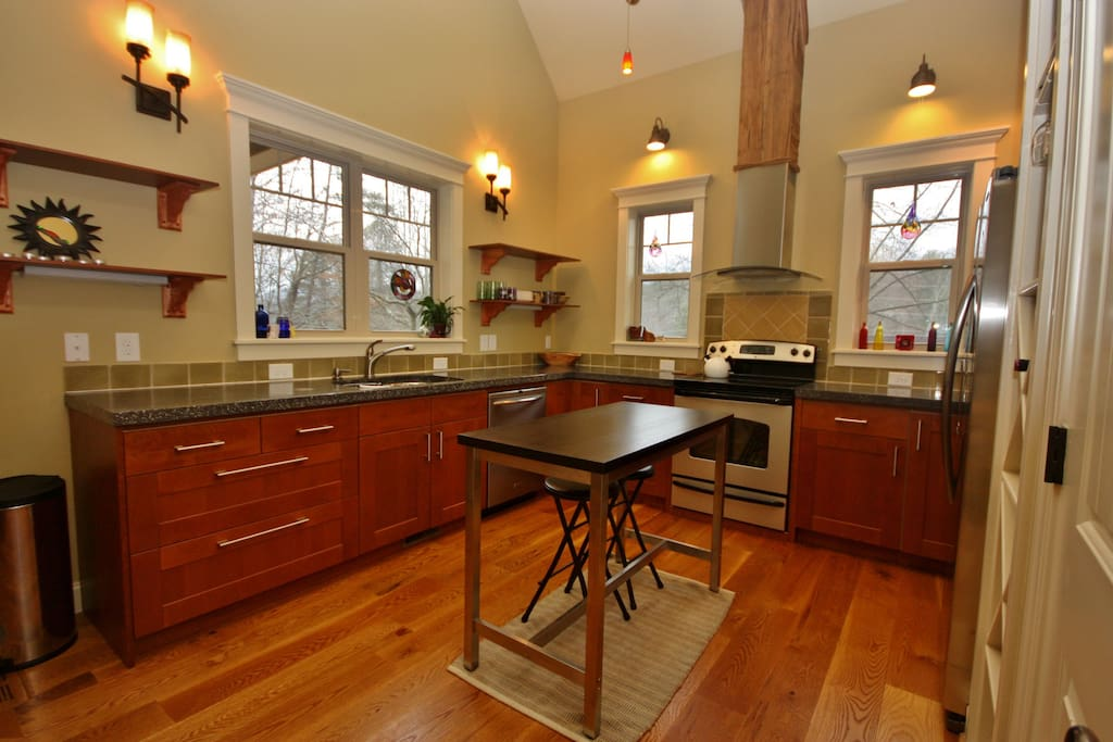Bright kitchen, concrete countertops, all stainless steel, oak flooring