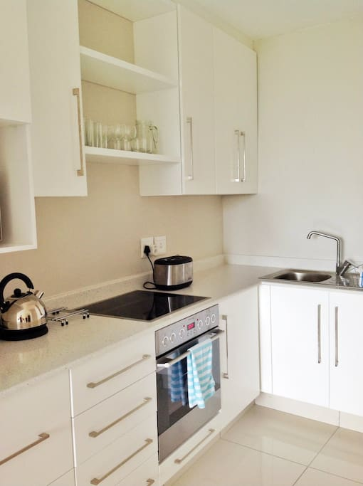 Open plan fully fitted kitchen, with oven, hob and microwave