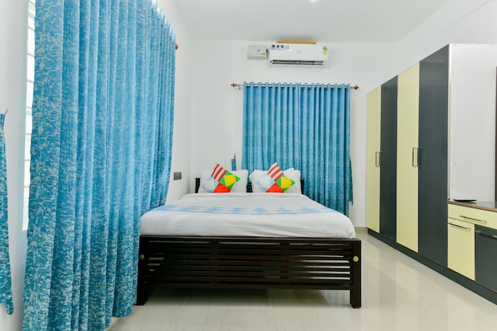 Master bed room with King size bed, extra chair and attached wash room.