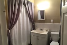 Immaculately maintained bathroom with rain shower and natural light.